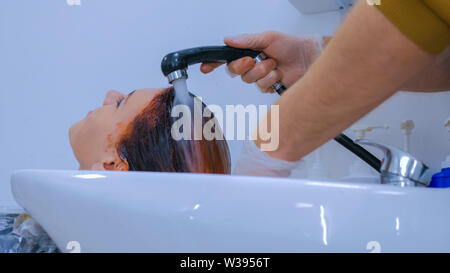 Hairdresser washing hair of woman client - Stock Image
