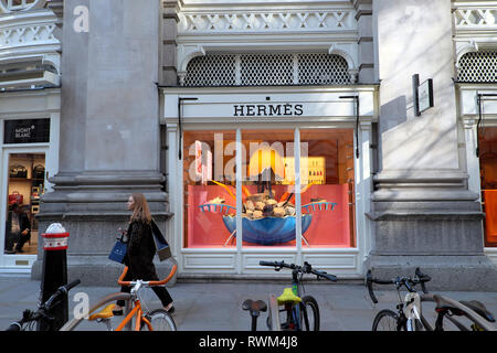 A fashionable woman walking outside the Hermès Paris store boutique exterior shop window in Royal Exchange, City of London England UK  KATHY DEWITT - Stock Image