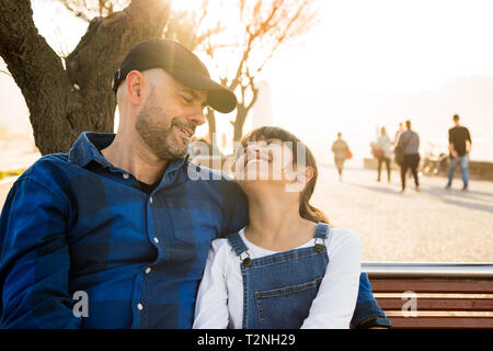 Father and daughter sitting on a bench on the waterfront looking at each other tenderly in a sunny day - Stock Image