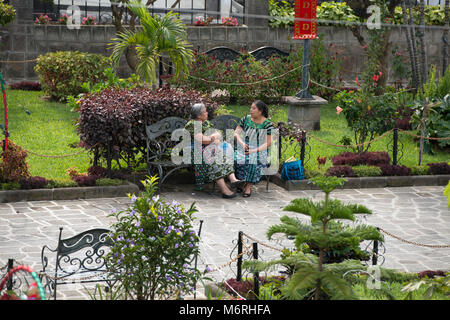 Two indigenous, ethnic Tz'utujil Maya women sitting on a park bench, talking in Santiago de Atitlán, Sololá - Stock Image