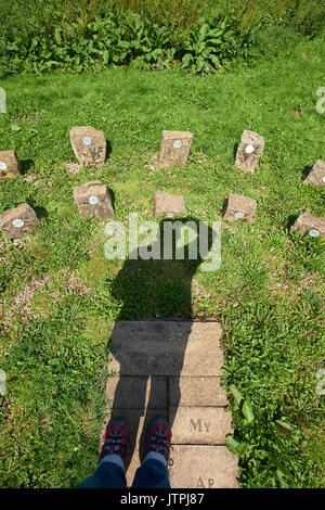 Shadow of an adult man male acts as the gnomon on a human sundial. Shadow cast on dial of stones. Two rows of stones for Daylight Saving Time DST. - Stock Image