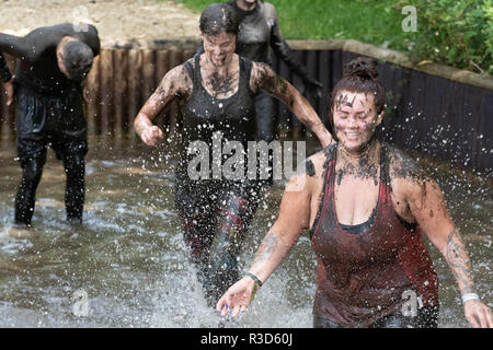 Rather muddy ladies and gentlemen splashing through a water crossing - Stock Image