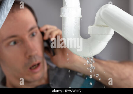 Shocked Young Man Calling Plumber To Fix Sink Pipe Leakage In Kitchen - Stock Image
