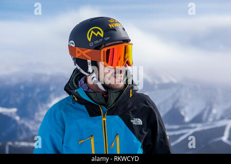 A skier smiling after reaching the summit of La Capa before the ride down on fresh powder. - Stock Image