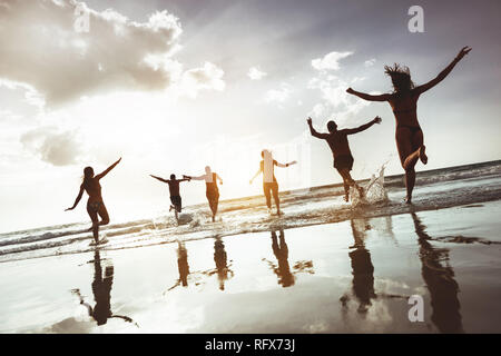 Big group of happy friends runs and jumps at sunset beach. Six active silhouettes against sea beach - Stock Image