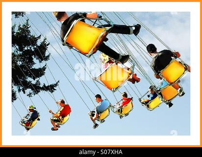Colorful amusement park chair ride with bright yellow seats - Stock Image
