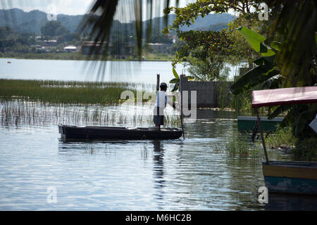 An indigenous, ethnic Itza Maya man in a boat making a living from fishing on Lake Peten, Guatemala. - Stock Image