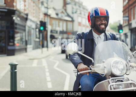 Smiling young businessman in helmet riding motor scooter on urban street - Stock Image