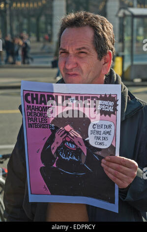 Geneva, Switzerland. 8th January 2015. A Swiss journalist holds up a cover of a past issue of Charlie Hebdo during - Stock Image