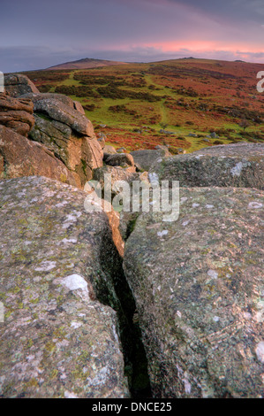 Looking from the summit outcrops of Bonehill Rocks toward Rippon Tor and Top Tor, as the afterglow of sunset gently - Stock Image