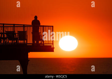Aberystwyth Wales UK, Sunday 14 July 2019  UK Weather: People silhouetted against the orange colour of the sunset as they stand on  the seaside pier  in Aberystwyth at the end of a warm summers day  in west Wales.   photo credit: Keith Morris/Alamy Live News - Stock Image