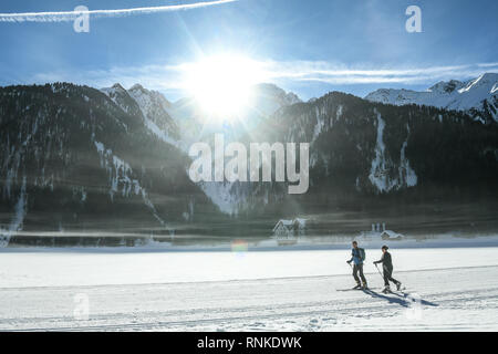 Anterselva lake, Pusteria valley, South Tyrol, Italy - February 16, 2019:  Two ski mountaineers ski on the Anterselva frozen lake as the early morning - Stock Image