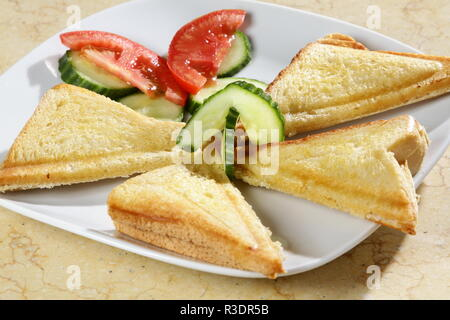 A shot of three triangle sandwiches with tomatoe and cucumber on the side. - Stock Image