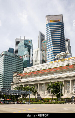 Singapore - 21st December 2018: Traffic waiting at a stop light outside the Fullerton Hotel. City tower blocks are in the background. - Stock Image