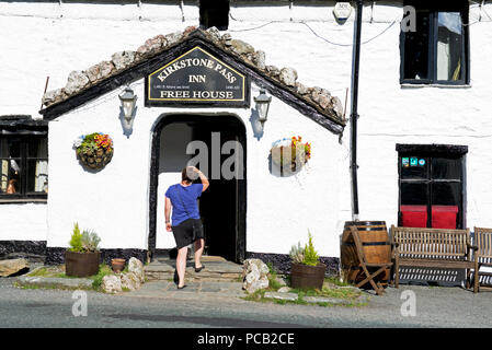 Young woman walking into the Kirkstone Pass Inn, Lake District National Park, Cumbria, England UK - Stock Image