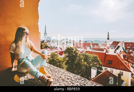 Woman sightseeing Tallinn city landmarks  vacations in Estonia travel lifestyle girl tourist relaxing at viewpoint Old Town aerial view architecture - Stock Image