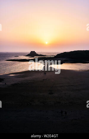 Sunset over small island and tiday causeway at St Malo, Brittany, France - Stock Image