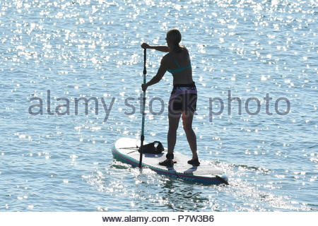Worthing, UK. Sunday 8th July 2018. A woman paddleboards at sea on a very warm morning in Worthing, on the South Coast. Credit: Geoff Smith / Alamy Live News. - Stock Image
