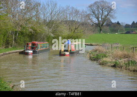 The Oxford Canal meanders through the Warwickshire countryside near the village of Wormleighton as a narrow boat sails along it. - Stock Image