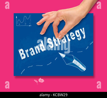 A hand picking up a Brand Strategy concept on a colorful drawing board. - Stock Image