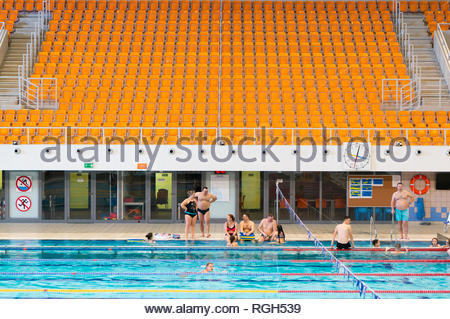 Poznan, Poland - January 26, 2019: People at a swimming pool with a empty tribune in the Termy Maltanskie. - Stock Image