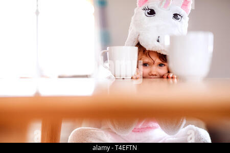 A portrait of happy small girl in unicorn mask sitting at the table at home. - Stock Image