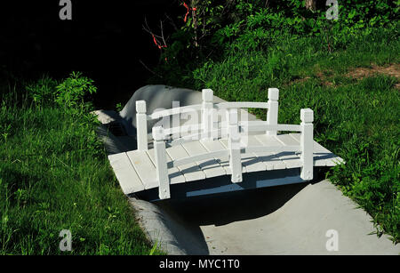 Small footbridge across drainage channel. - Stock Image