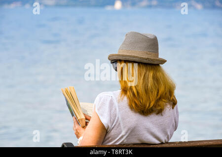 TORRI DEL BENACO, LAKE GARDA, ITALY - SEPTEMBER 2018: Person reading a book sitting on a bench lakeside in the town of Torri del Benaco on Lake Garda - Stock Image