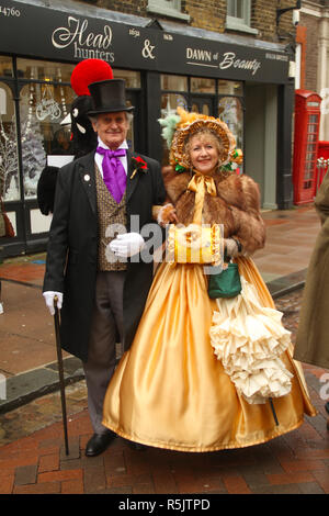 Rochester, Kent, UK. 1st December 2018: A couple in Period Victorian custume ahead of the mina parade on Rochester High Street. Hundreds of people attended the Dickensian Festival in Rochester on 1 December 2018. The festival's main parade has participants in Victorian period costume from the Dickensian age. The town and area was the setting of many of Charles Dickens novels and is the setting to two annual festivals in his honor. Photos: David Mbiyu/ Alamy Live News - Stock Image