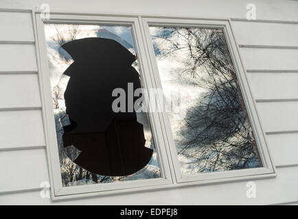 vandalized broken window on house - Stock Image