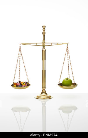 Weighing Scales with Apple and Sweets - Stock Image