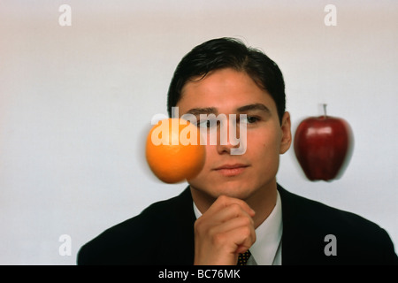 businessman in suit comparing orange & apple - Stock Image