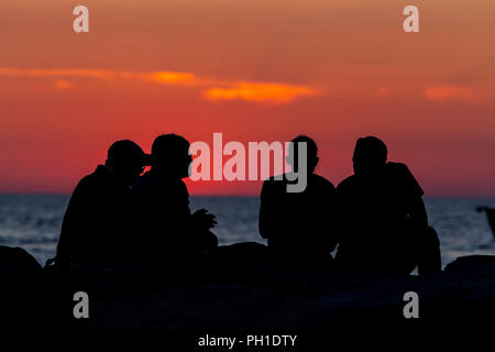 People sit on the jetty after watching the sunset over the Vineyard Sound at Menemsha Beach in Chilmark, Massachusetts on Martha's Vineyard. - Stock Image