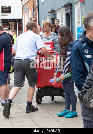 Postman making his way through the spectators to deliver - Stock Image