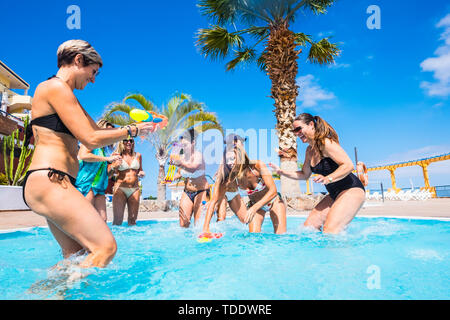 Joyful and friendship with group of women people having fun playing with water guns in the swimming pool - summer holiday vacation concept at resort - - Stock Image