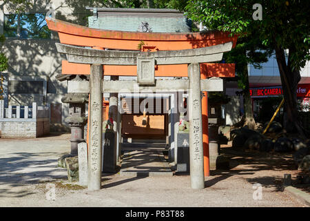Torii stone gates in Kego Shrine  n Tenjin, central Fukuoka, Japan. The shrine is surrounded by busy streets and modern buildings. - Stock Image