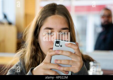 girl looking at mobile phone, Castellon - Stock Image