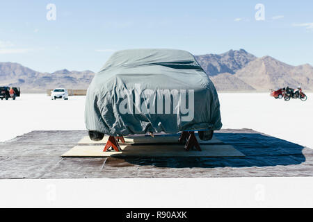 Race car covered with protective cloth in the Salt Flats - Stock Image