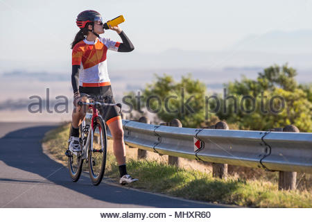 Female cyclist taking drink from water bottle on race bicycle on sunny open road - Stock Image