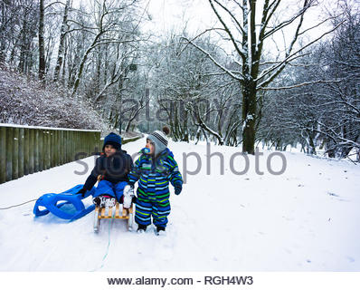 Poznan, Poland - January 26, 2019: Two young small boys with a plastic and wooden sled on a footpath with snow at a park on a cold winter day. - Stock Image