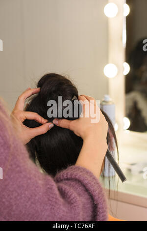 Hands of hairdresser form high tuft of hair. Workshop session to create upper bun hairstyle. Apprenticeship concept. Beauty industry. Space for text - Stock Image