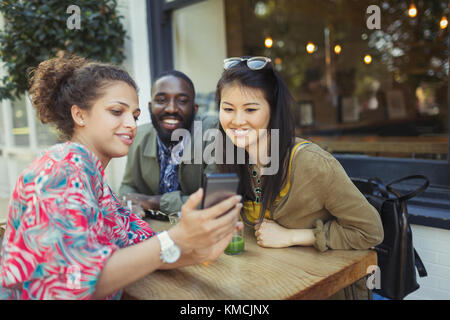 Young friends using cell phone at sidewalk cafe - Stock Image