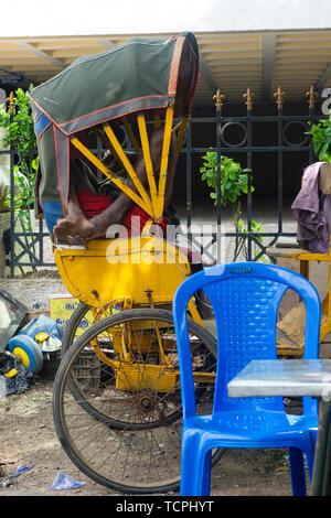 Poverty in Chennai, India, where a man sleeps in a tuk tuk - Stock Image