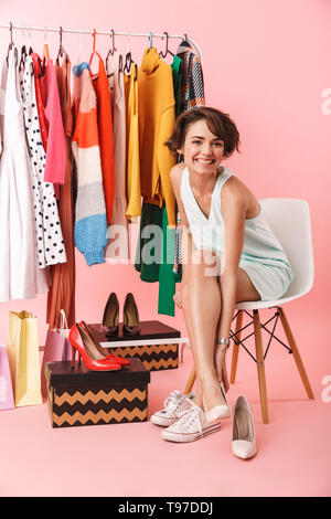 Image of a pretty woman stylist posing isolated over pink wall background near a lot of clothes. - Stock Image