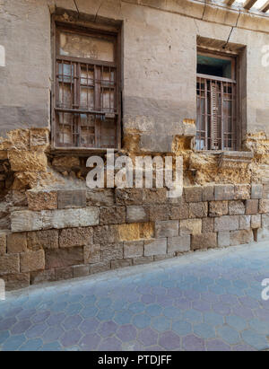 Angled view of two adjacent broken windows and grunge stone bricks wall in abandoned Darb El Labana district, Cairo, Egypt - Stock Image