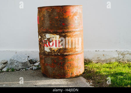 An old rusty oil barrel in the sunlight - Stock Image