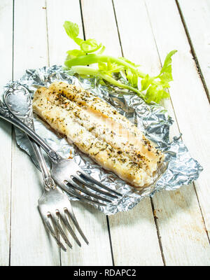 Baked fish fillet with spices and celery. On a white wooden background. - Stock Image