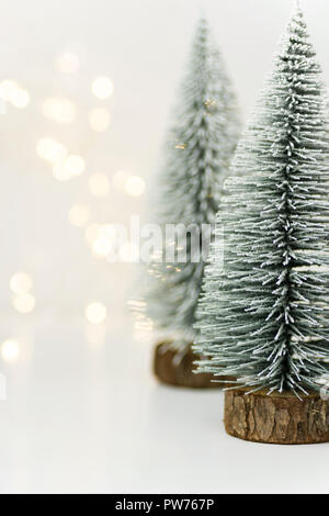 Fluffy covered with snow Christmas trees in forest golden bokeh garland lights white background. New Years holiday magic atmosphere. Greeting card ban - Stock Image