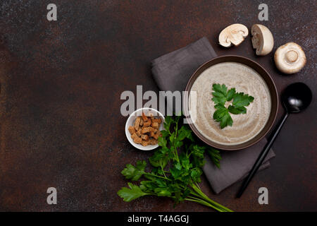 mushroom soup in a brown bowl, parsley, croutons on a brown background. view from above. copy space - Stock Image