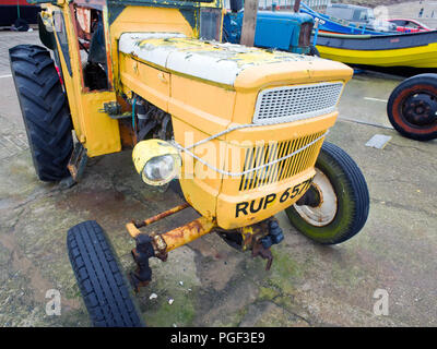 Old Yellow Tractor Filey Sea front UK - Stock Image